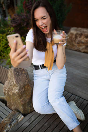 free young woman drinking coffee and chatting in a smartphone while sitting on a bench in a summer park.