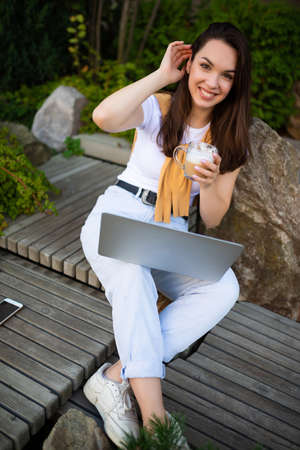 happy woman freelancer on coffee break resting outdoors sitting on a bench.