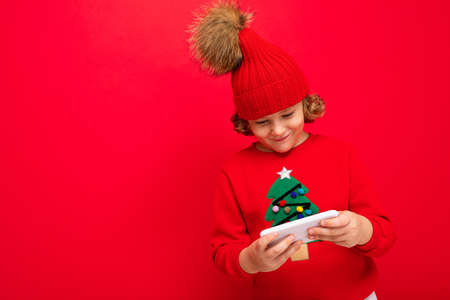 a young man with a smartphone in his hands against the background of a red wall, in a knitted hat and a sweater with a Christmas tree