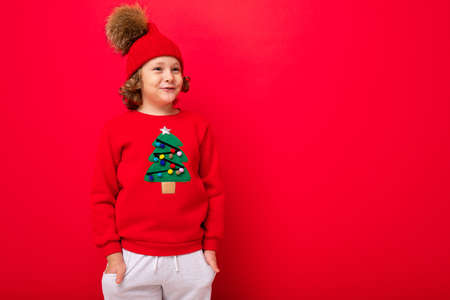 cool teenager in a red Christmas sweater fooling around against the background of a red wall, a warm hat and a sweater with a Christmas tree.