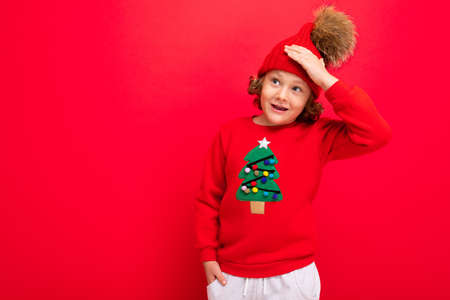 cheerful funny boy on a red background in a warm hat and sweater with a Christmas tree.
