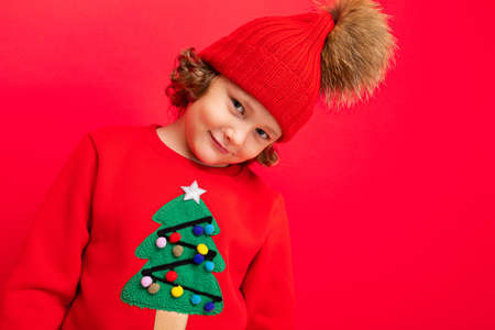 cool boy with curls on a red background in a sweater with a christmas tree.