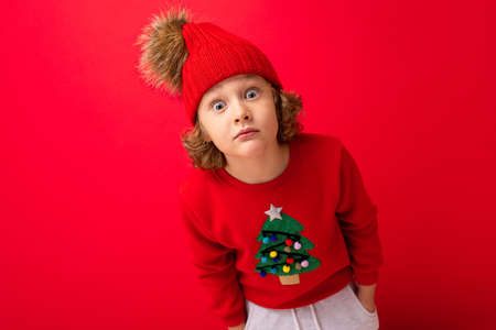 cute blond boy in warm hat and christmas sweater on red background with smile on his face.