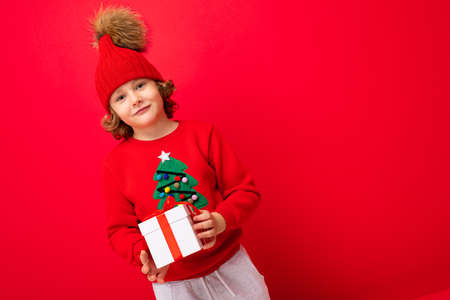 a cool boy with curls on a red wall background in a sweater with a Christmas tree holding a gift box in his hands. Banco de Imagens