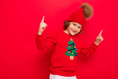 boy model on a red background, portrait of a cool blonde with curls in a sweater with a Christmas tree. Banco de Imagens