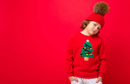 cool blond kid in warm hat and sweater with christmas tree on red background fooling around, christmas concept.