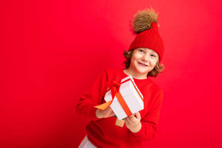 curly blond boy with a gift in his hands on a red background.