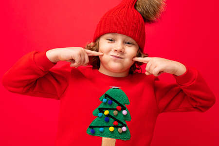 boy model on a red background, portrait of a cool blonde with curls in a sweater with a Christmas tree. 免版税图像