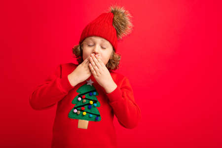 emotional portrait of a teenager on a red background in a new year costume.
