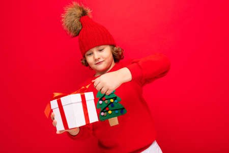 a cool boy with curls on a red wall background in a sweater with a Christmas tree holding a gift box in his hands. 免版税图像