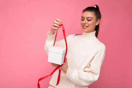 Beautiful happy young brunette woman isolated over colourful background wall wearing stylish casual clothes holding gift box and looking to the side.