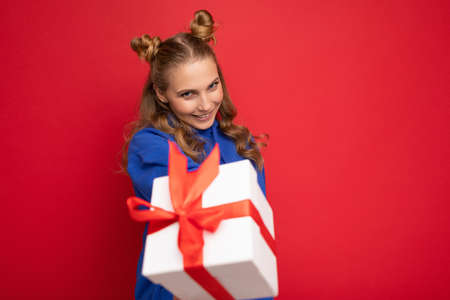 Charming happy funny joyful young blonde woman isolated over red background wall wearing blue trendy hoodie holding gift box and looking at camera.