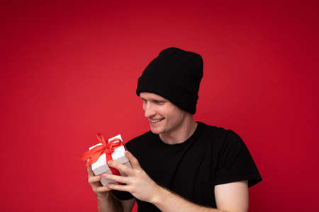 Handsome happy smiling young man isolated over red background wall wearing black hat and black t-shirt holding white gift box with red ribbon and looking at present.