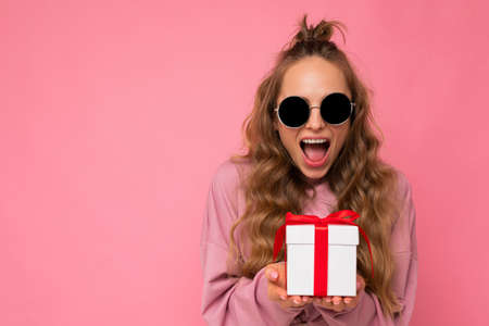 Photo shot of pretty positive surprised young blond woman isolated over colourful background wall wearing trendy outfit look holding gift box and looking at camera. Copy space