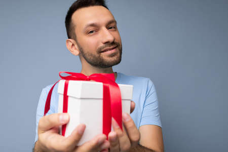 Portrait shot of handsome happy brunette unshaven young male person isolated over blue background wall wearing blue t-shirt holding white gift box with red ribbon and looking at camera.