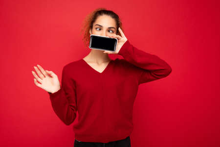 Photo of happy funny young female person wearing dark red sweater isolated over red background holding smartphone and showing mobile phone screen with copy space for cutout.