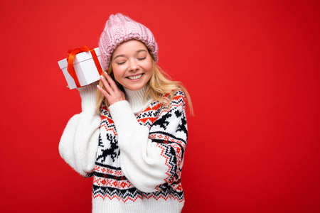 Shot of attractive positive smiling young blonde woman isolated over colourful background wall wearing everyday trendy outfit holding gift box and having fun. Copy space, mockup