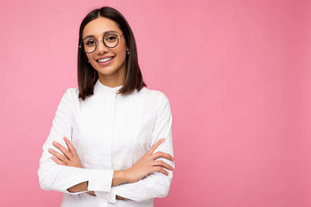 Photo shot of beautiful smiling young brunette woman wearing casual clothes and stylish optical glasses isolated over colorful background looking at camera. copy space