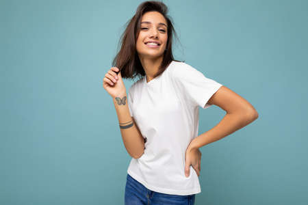 Portrait of young beautiful happy smiling brunette woman wearing trendy white t-shirt with empty space for mock up.