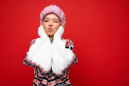Photo of beautiful happy funny amazing young blonde woman isolated over red background wall wearing winter sweater and pink hat looking at camera and giving kiss. Empty space