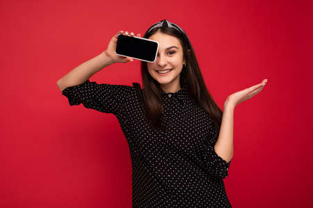 Photo of smiling beautiful brunette girl standing isolated over red wall wearing casual stylish black clothes showing mobile phone with empty screen for cutout looking at camera. 写真素材
