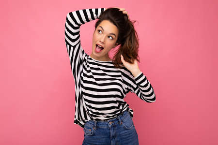 Young beautiful brunet woman. Trendy lady in casual striped longsleeve. Positive female shows facial sincere emotions. Funny model isolated on pink background with free space.