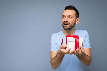 Shot of handsome joyful brunette unshaven young man isolated over blue background wall wearing blue t-shirt holding white gift box with red ribbon and looking to the side. Copy space