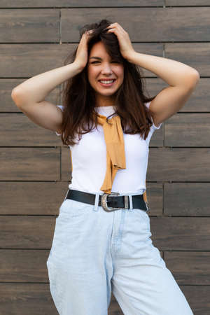 Vertical ptoto of young beautiful positive happy brunette woman standing against brown wall in the street and wearing stylish outfit.