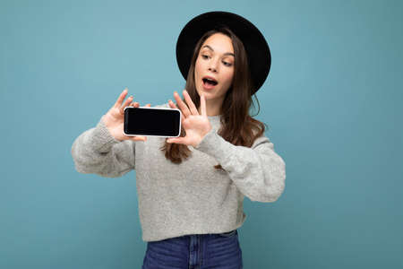 Attractive young smiling woman wearing black hat and grey sweater holding smartphone looking down isolated on background.Mock up, cutout 写真素材