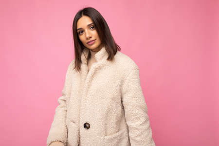 European beautiful young brunette woman wearing stylish beaige warm coat isolated over pink background with copy space. Fashion concept.