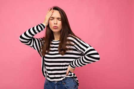 Photo of young sad upset tired beautiful brunette woman with sincere emotions wearing casual striped pullover isolated on pink background with copy space and having headache.