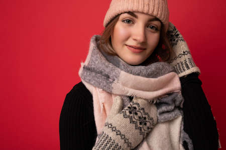 Closeup photo of beautiful happy cute young brunette woman isolated over red background wall wearing winter scarf mittens and warm hat looking at camera.