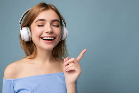 Closeup photo of beautiful positive smiling young blonde woman wearing blue crop top isolated over blue background wall wearing white wireless bluetooth earphones listening to cool music and enjoying.