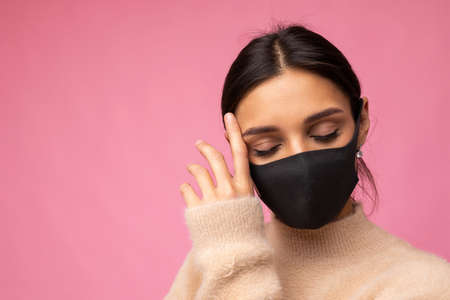 Woman wearing stylish protective face mask, posing on pink background. Trendy fashion accessory during quarantine of coronavirus pandemic. Close up studio portrait. Copy, empty space for text. Standard-Bild