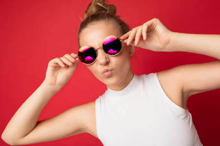 Photo shot of beautiful young blonde woman wearing casual clothes and stylish sunglasses isolated over colorful background looking at camera.