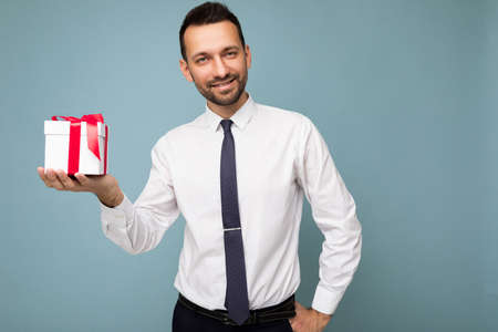 Photo shot of handsome positive brunette unshaven young man isolated over blue background wall wearing white shirt holding white gift box with red ribbon and looking at camera. Standard-Bild