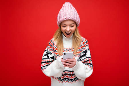 Photo of attractive crazy amazed surprised young woman wearing casual stylish clothes standing isolated over background with copy space holding and using mobile phone looking at device display. Standard-Bild