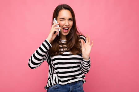 Winking Pretty happy young woman speaking on the phone wearing striped sweater isolated over background with copy space showing ok gesture looking at camera.