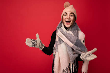 Photo of beautiful happy amazing funny young brunette woman isolated over red background wall wearing winter scarf mittens and warm hat looking at camera and having fun Foto de archivo