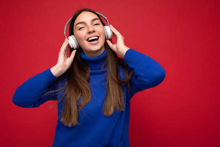 Attractive positive young brunette woman wearing blue sweater isolated over red background wall wearing white earphones listening to cool music and having fun