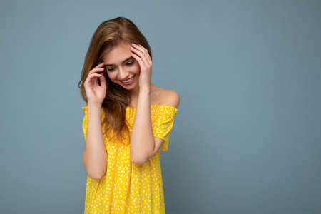 Young beautiful dark blonde woman with sincere emotions isolated on background wall with copy space wearing stylish summer yellow dress. Positive concept