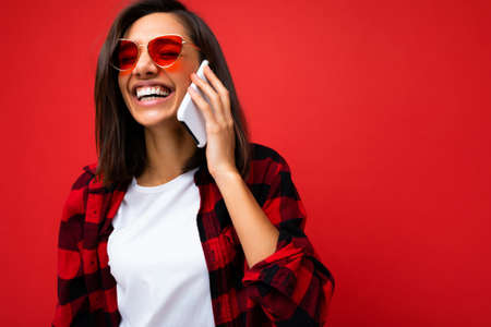 Closeup photo of Beautiful positive young brunette woman wearing stylish red shirt white t-shirt and red sunglasses isolated over red background talking on mobile phone looking at camera