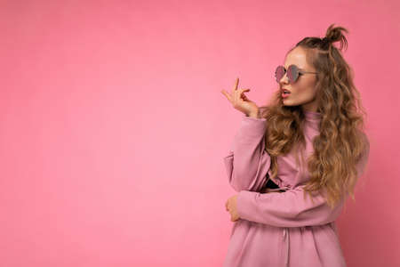 Attractive dissatisfied asking young blonde woman wearing everyday stylish clothes and modern sunglasses isolated on colorful background wall looking to the side and having doubts