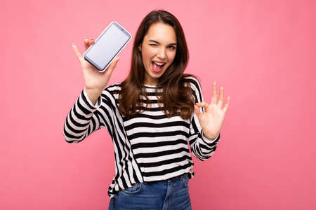 Winking beautiful happy young woman wearing striped sweater isolated over background with copy space showing ok gesture looking at camera showing mobile phone screen display Stock fotó