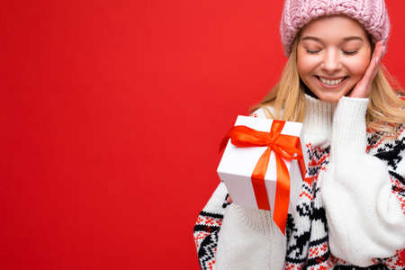 Closeup photo shot of beautiful happy smiling surprised young blonde woman isolated over red background wall wearing winter sweater and pink hat holding white gift box with red ribbon