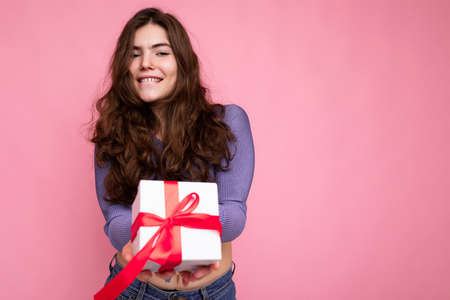 Shot of attractive positive smiling young brunette woman isolated over colourful background wall wearing everyday trendy outfit holding gift box and looking at camera Stock fotó