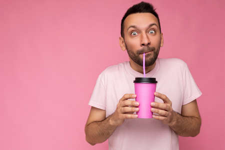 Amazed handsome funny joyful young brunette unshaven male person with beard wearing white t-shirt isolated over pink backgroung wall holding paper cup for mock up and drinking looking at camera Stock fotó