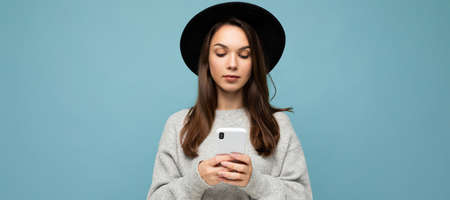 Beautiful young brunette woman wearing black hat and grey sweater holding smartphone looking down at phone texting isolated on background