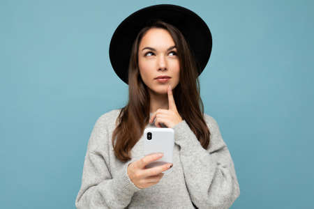 Beautiful young brunette woman thinking wearing black hat and grey sweater holding smartphone looking up texting isolated on background