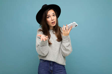 Beautiful young asking dissatisfied brunette woman wearing black hat and grey sweater holding smartphone looking at camera isolated on background